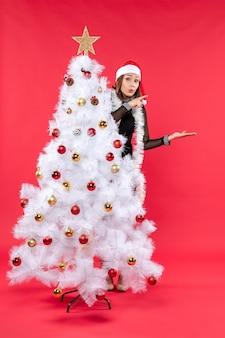 Neujahrsstimmung mit überraschtem schönem mädchen in einem schwarzen kleid mit weihnachtsmannhut, der sich hinter weihnachtsbaum versteckt