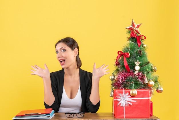 Neujahrsstimmung mit überraschter junger frau mit geschmücktem weihnachtsbaum im büro auf gelb