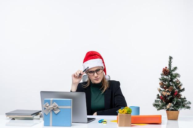 Neujahrsstimmung mit unentschlossener blonder frau mit einem weihnachtsmannhut, der an einem tisch mit einem weihnachtsbaum und einem geschenk auf ihm auf weißem hintergrund sitzt