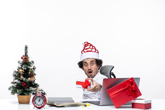 Neujahrsstimmung mit unzufriedenem schockiertem jungen geschäftsmann mit weihnachtsmannhut, der im büro sitzt und sein geschenk auf weißem hintergrund erhöht