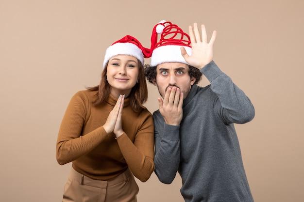 Neujahrsstimmung und partykonzept - junges aufgeregtes reizendes paar, das vereinte weihnachtsmannhüte auf grau vereint