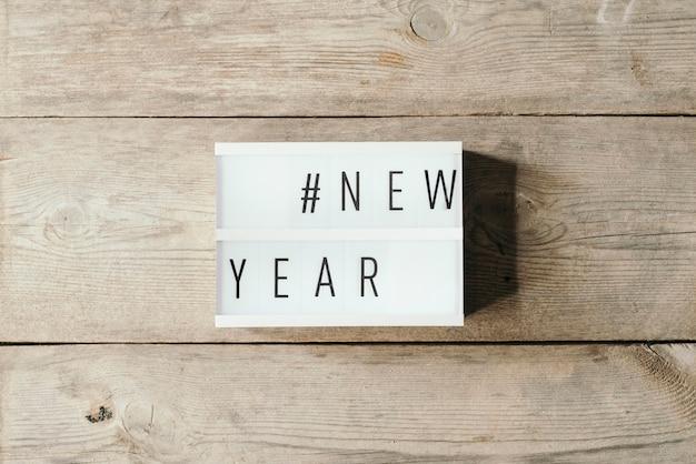 Neujahrstext in led-tafel mit holzhintergrund