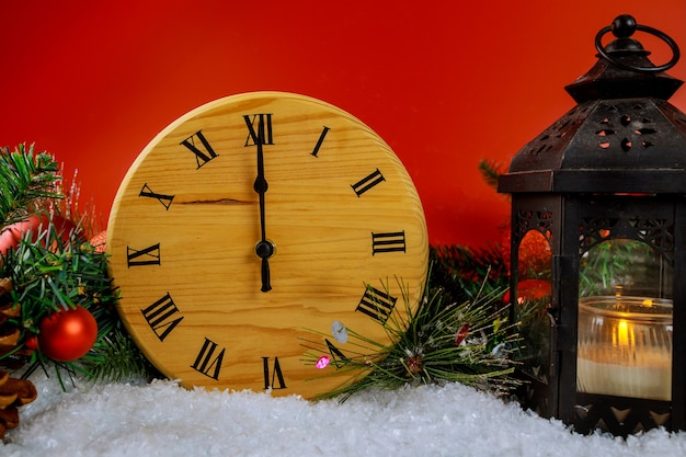 Neujahrsuhr countdown mit weihnachtslaterne auf tannenzweigdekoration schneebedeckter fichtenzweig rot