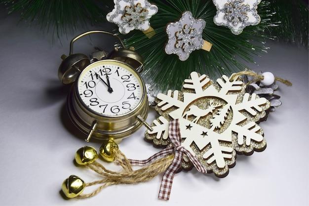 Neujahrsuhr dekoriert mit hölzernen schneeflocken mit funkeln und ornamenten im hintergrund. weihnachts- und silvesterfeierkonzept.