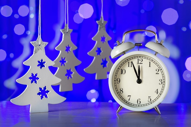 Neujahrsuhr mit dekoration auf blauem hintergrund. frohes neues jahr komposition.