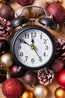 Neujahrsuhr mit zeigern um zehn bis zwölf mit weihnachtsplastikkugeln und weihnachtsspielzeug