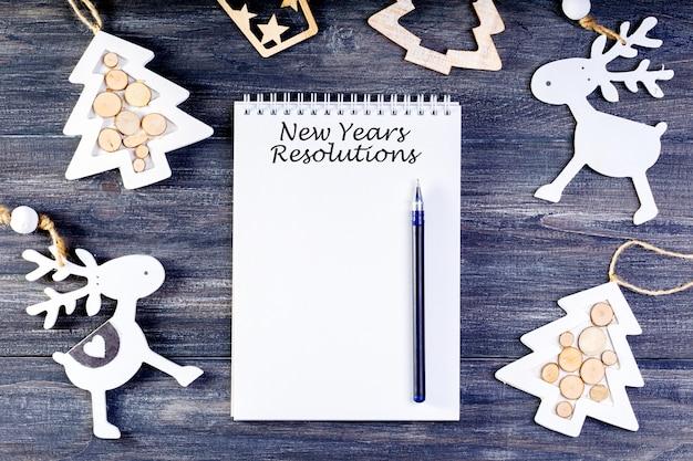 Neujahrsvorsätze mit notizbuch und dekoration auf holz