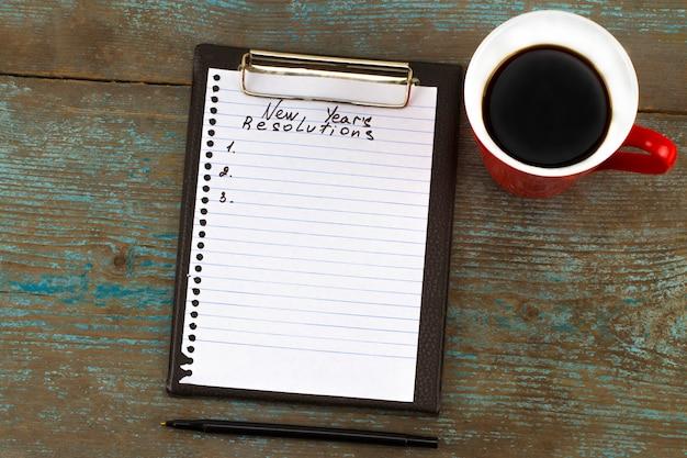 Neujahrsvorsatz auf einem notizblock und einem stift geschrieben. neujahrsvorsätze konzept.
