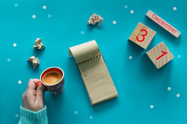 Neujahrsvorsatzkonzept, hand mit kaffee, notizbuch, holzkalender und kaffee auf blau
