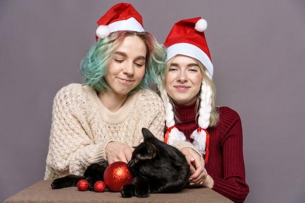 Neujahrsweihnachtsmädchen in weihnachtsmannmützen mit lustigen blonden haaren, nahaufnahme einer schwarzen katze im t...