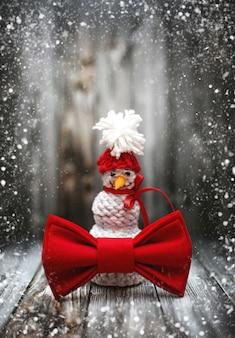 Neujahrswinterschneemanndekoration mit schnee auf schwarzer holzoberfläche. feiertags-neujahrspostkartenrahmenentwurf mit kopienraum