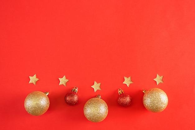 Neujahrswohnung lag. glänzende goldene und rote weihnachtskugeln und sterne auf einem leuchtend roten festlichen hintergrund.