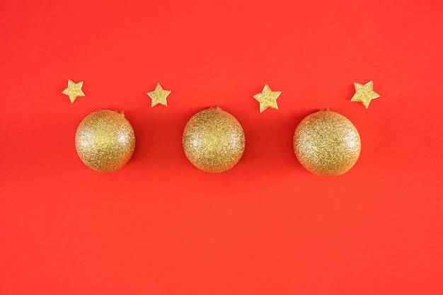 Neujahrswohnung lag. glänzende goldene weihnachtskugeln und sterne auf einem leuchtend roten festlichen hintergrund.