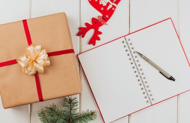 Neujahrswunschliste, weihnachtsdekoration und geschenkbox. notizbuch und bleistift.