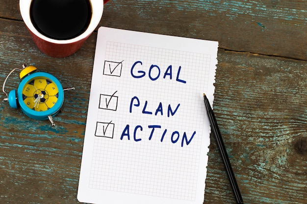 Neujahrsziel, plan, aktion - text auf notizblock mit tasse kaffee. geschäftsmotivation, inspirationskonzepte.