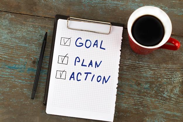 Neujahrsziel, plan, aktion. text auf notizblock mit tasse kaffee. geschäftsmotivationskonzepte