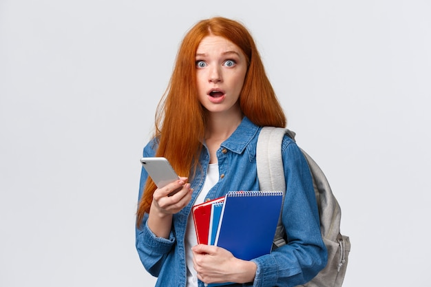Neuling mädchen mit roten langen haaren, weiß nicht, wo ihre klasse, fragend und verwirrt, starren besorgt und halten smartphone, rucksack und notizbücher, ahnungslos, wo gehen, weiß