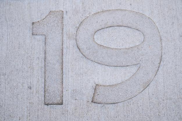 Neunzehn (19) nummer auf betonboden gestempelt.