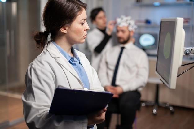 Neurologe-wissenschaftler, der die gehirntomographie des patienten mit headset betrachtet, high-tech-scan auf dem bildschirm. arzt, der elektroden hinzufügt. moderne neurowissenschaften.