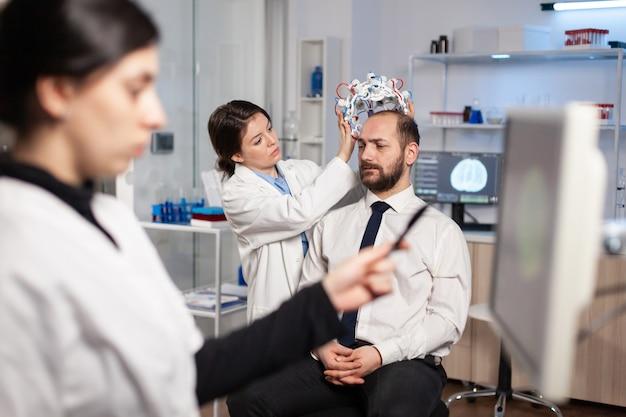 Neurologieforscher, der während des studiums das gehirn-headset an den patienten anpasst und das nervensystem untersucht. high-tech-tomographiesensoren, neurowissenschaftler.