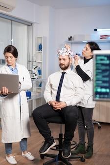 Neurologische forscherinnen im frauenteam arbeiten zusammen an der entwicklung einer behandlung zur diagnose von hirnerkrankungen, erklären eeg-ergebnisse, gesundheitszustand, gehirnfunktionen, nervensystem und tomographie-scan