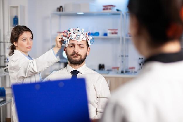 Neurowissenschaftlicher arzt, der auf der zwischenablage behandlung gegen hirnerkrankungen zeigt, die die diagnose der krankheit des patienten erklären. frau, die im neurologischen wissenschaftlichen labor sitzt und funktionsstörungen des nervensystems behandelt