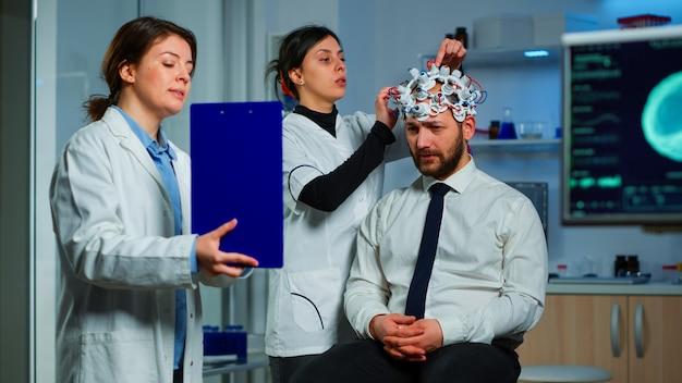Neurowissenschaftlicher arzt, der auf der zwischenablage behandlung gegen hirnerkrankungen zeigt, die die diagnose der krankheit des patienten erklären. frau, die im neurologischen wissenschaftlichen labor sitzt und störungen des nervensystems behandelt