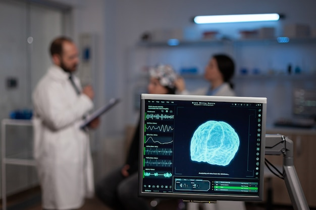 Neurowissenschaftlicher arzt mit zwischenablage, der patienten mit eeg-headset behandlung gegen hirnerkrankungen zeigt. frau, die im neurologischen wissenschaftlichen labor sitzt und störungen des nervensystems behandelt.