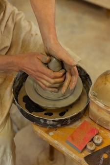 Neuschöpfung bilden. genauer professioneller töpfermeister mit rad im studio, während topf aus nassem ton hergestellt wird