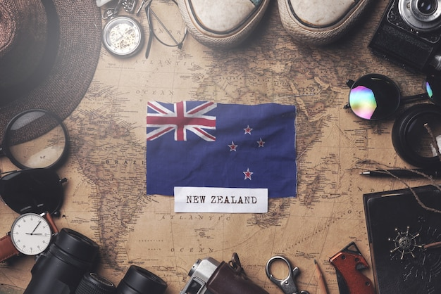 Neuseeland-flagge zwischen dem zubehör des reisenden auf alter weinlese-karte. obenliegender schuss