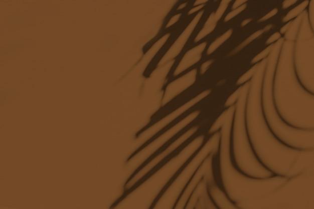 Neutrale blumenkomposition mit tropischer palmzweig-silhouette auf dunkelbraun