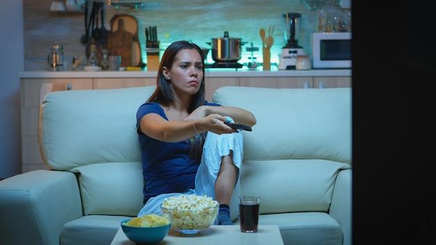 Nevous dame wechselt die kanäle auf einer gemütlichen couch. gelangweilte, wütende allein zu hause spät in der nacht frau entspannt vor dem fernseher liegend auf einem bequemen sofa mit fernbedienung und sucht nach einem comedy-film.