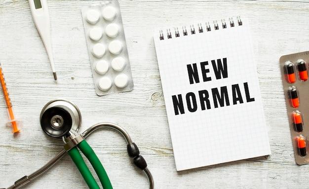 New normal steht in einem notizbuch auf einem weißen tisch neben pillen und einem stethoskop. medizinisches konzept