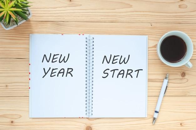 New year new start mit notebook, schwarze kaffeetasse, stift