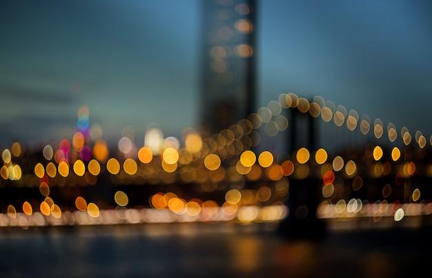 New york city - die schöne verwischte vogelperspektivestadt beleuchtet die nachtansichtskyline, abstrakt über manhattan mit manhattan-brücke