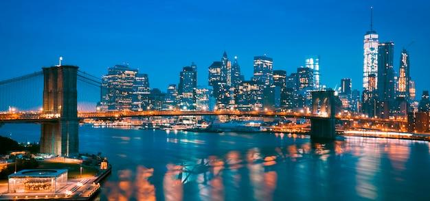 New york city manhattan midtown in der abenddämmerung mit brooklyn bridge.