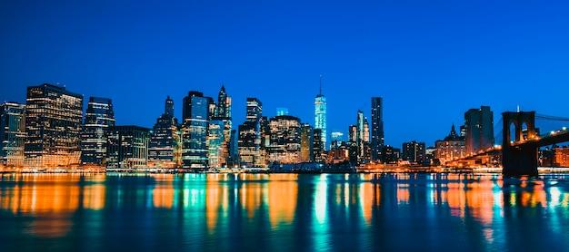 New york city manhattan midtown in der abenddämmerung mit wolkenkratzern beleuchtet über east river