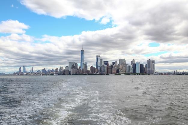 New york, usa - 15. juni 2018: schauen sie auf das segelboot, das in den new yorker hafengebäuden der insel manhattan im hintergrund kreuzt.