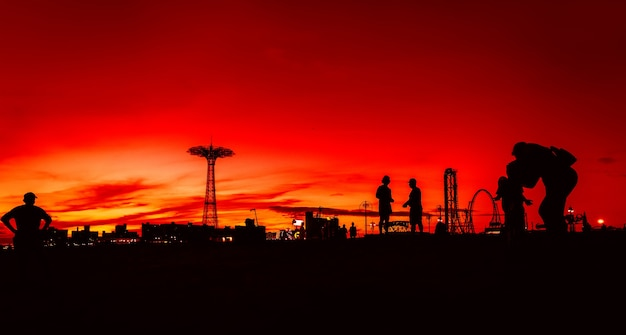 New york, usa - 22. september 2017: coney island beach in new york city. schattenbilder der leute und des fallschirmsprungturms auf einem sonnenuntergangshintergrund