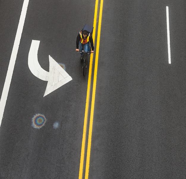New york, usa - 3. mai 2016: straßenmarkierungen auf asphalt auf der straße von manhattan in new york city. bewegungsverschmierter radfahrer bewegt sich entlang der straße. schillernder benzinfleck auf asphalt