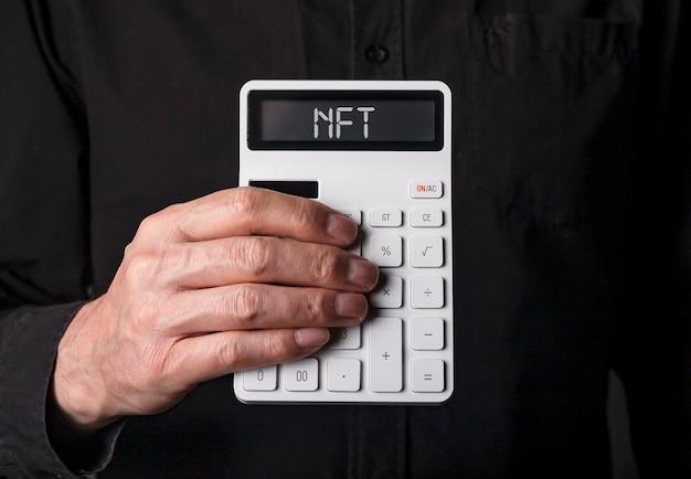 Nft akronym auf weißem taschenrechner in der hand auf schwarzem hintergrund