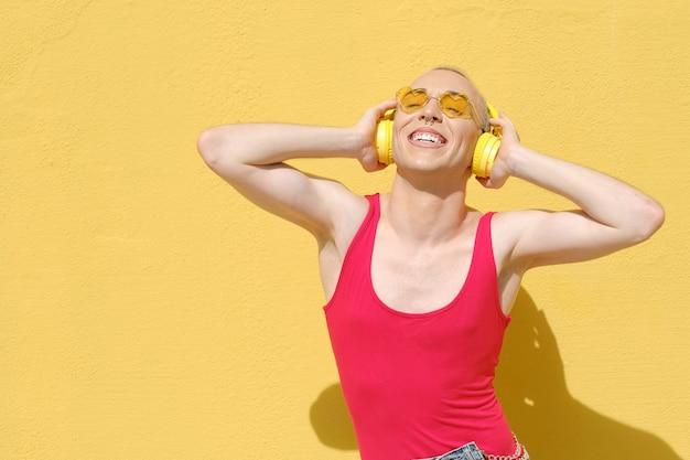 Nicht-binäre junge person, die lächelt, während sie im freien musik mit kopfhörern hört. urbanes lifestyle-konzept.