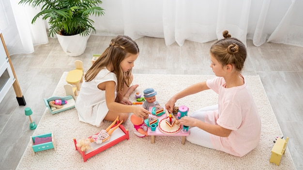 Nicht binäre kinder, die ein geburtstagsspiel mit einer babypuppe spielen
