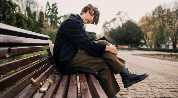 Nicht binäre person, die draußen auf einer bank sitzt