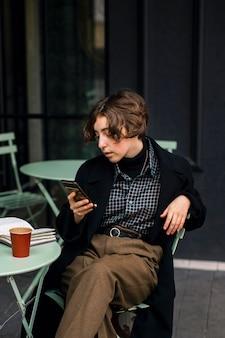 Nicht binäre person, die ein telefon überprüft
