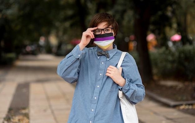 Nicht binäre person, die eine gesichtsmaske mit repräsentativer flagge trägt