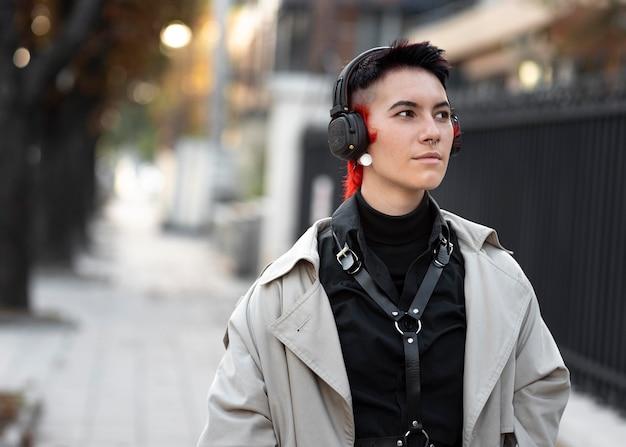 Nicht binäre person mit moderner frisur, die musik hört