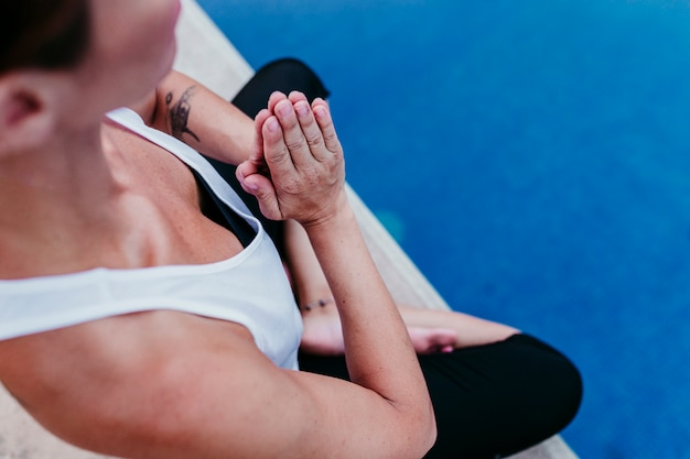 Nicht erkennbar an der jungen frau (fitness, yoga, gesunder körper) im schwimmbad