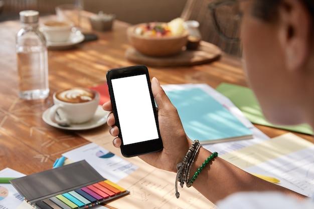 Nicht erkennbare ethnische junge frau hält modernes smartphone mit leerem bildschirm
