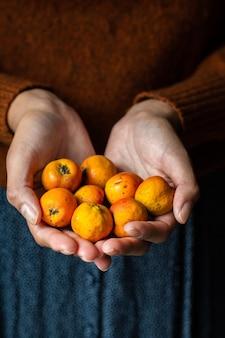 Nicht erkennbare frau, die einige tejocotes früchte hält